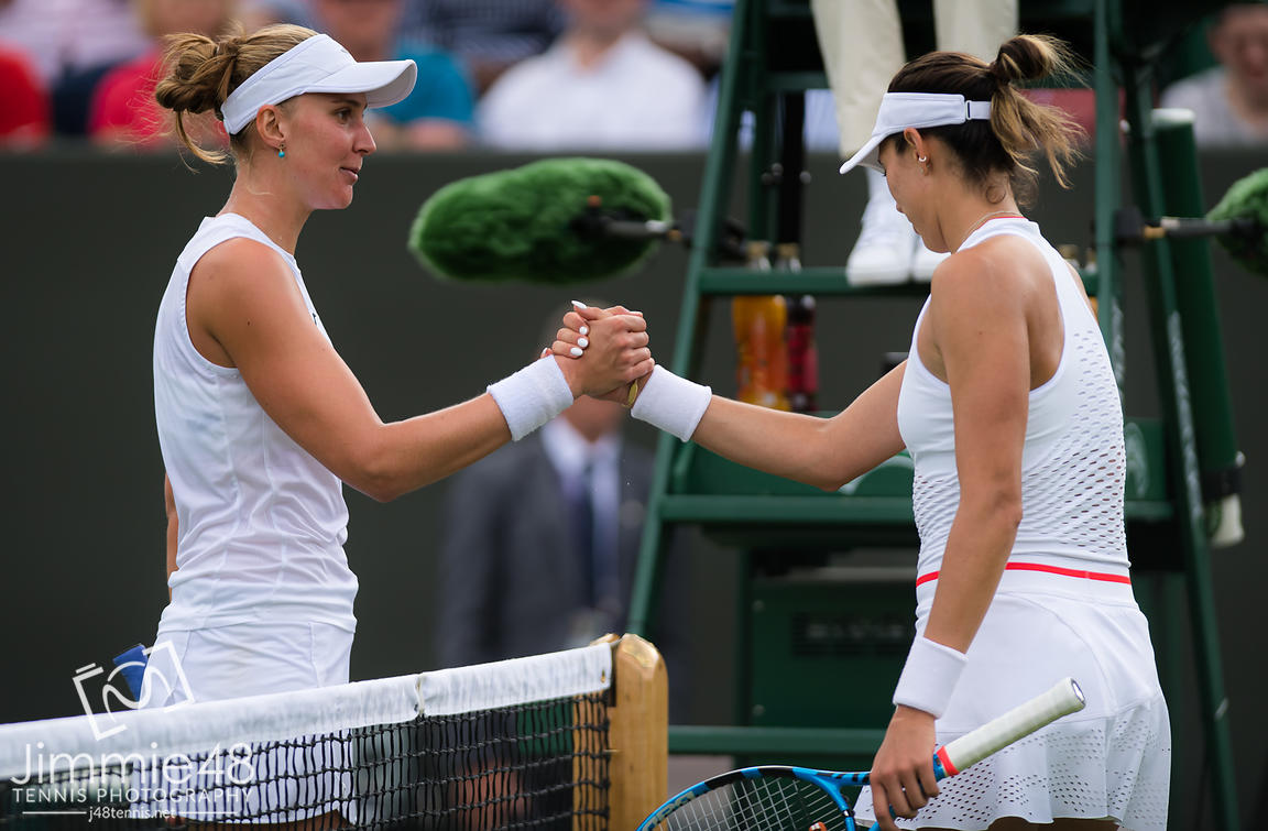 Beatriz Haddad Maia of Brazil & Garbine Muguruza of Spain at the net after their first-round match at the 2019 Wimbledon Championships Grand Slam Tennis Tournament
